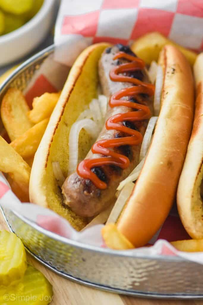 a beer brat in a bun in a tray surrounded by fries garnished with onions and topped with ketchup