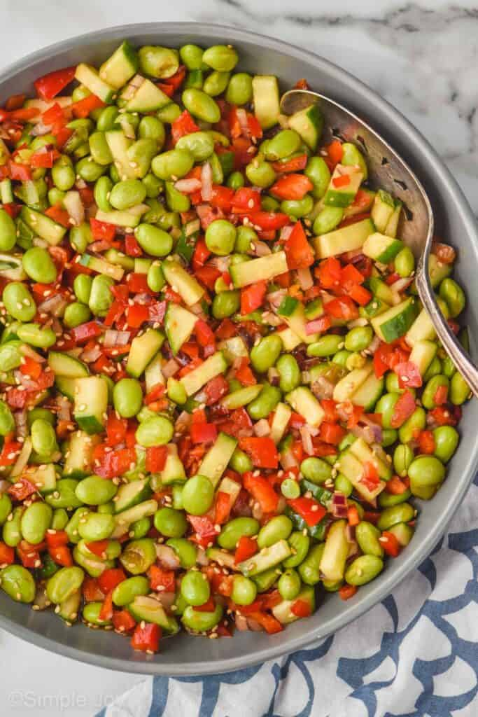 overhead view of an edamame salad, made and mixed, coated with dressing