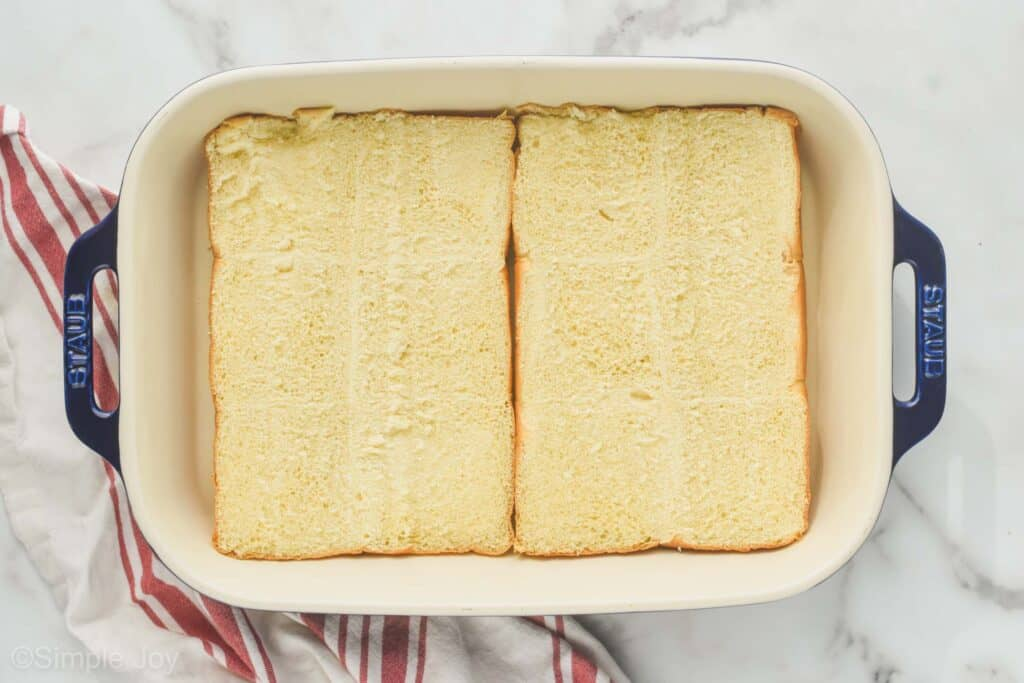 overhead of bottom half of rolls in a baking dish to make ham and cheese sliders
