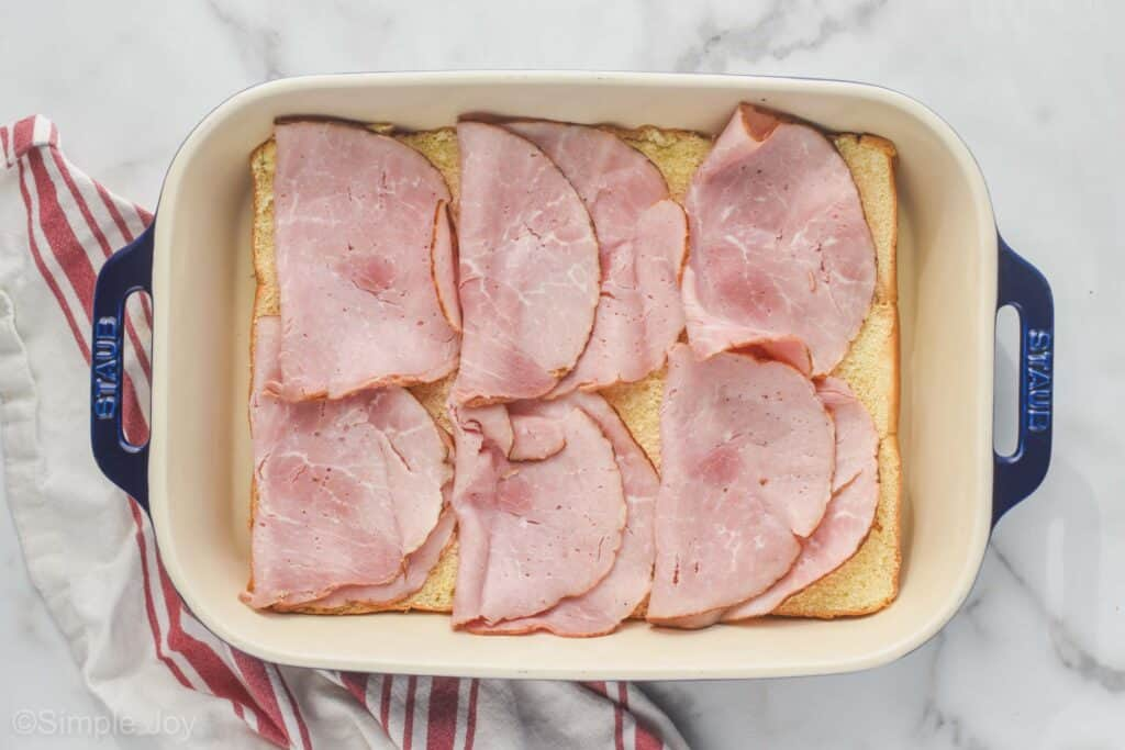 overhead of ham layered on the bottom of rolls to make ham and cheese sliders