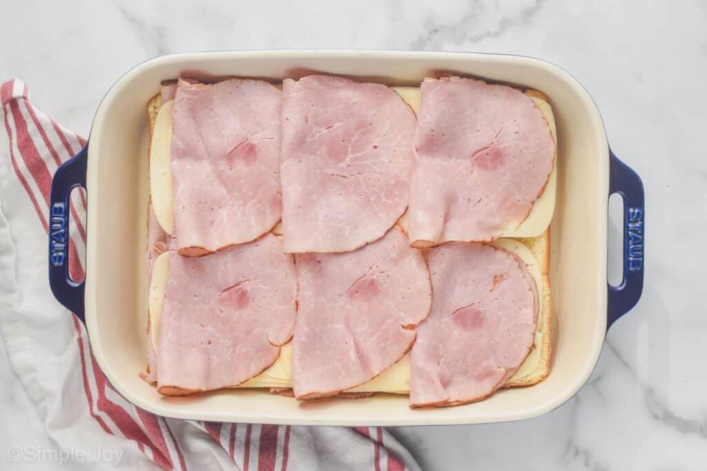 overhead of ham layered on Swiss cheese to make ham and cheese sliders