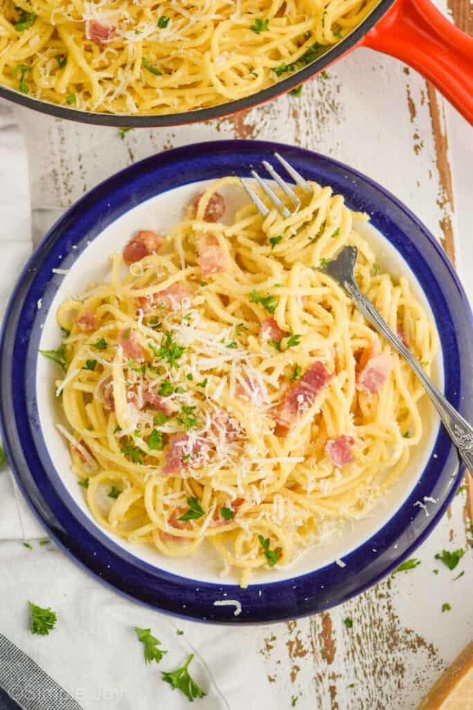 overhead view of a plate of pasta carbonara with a fork twirling the spaghetti, garnished with parmesan cheese and fresh parsley