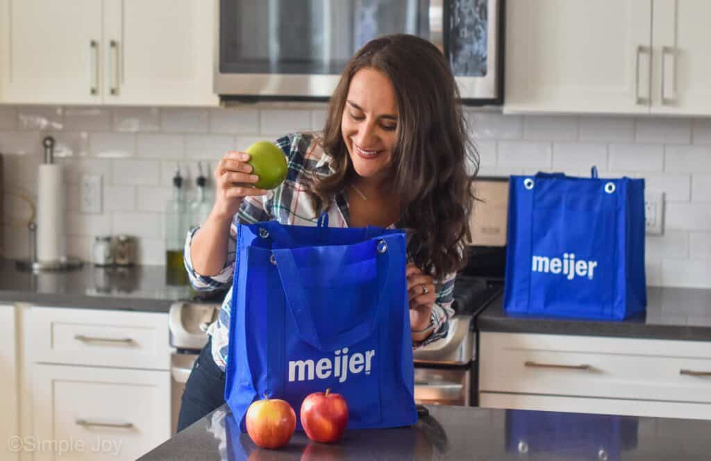 woman taking a apple out of a Meijer grocery bag
