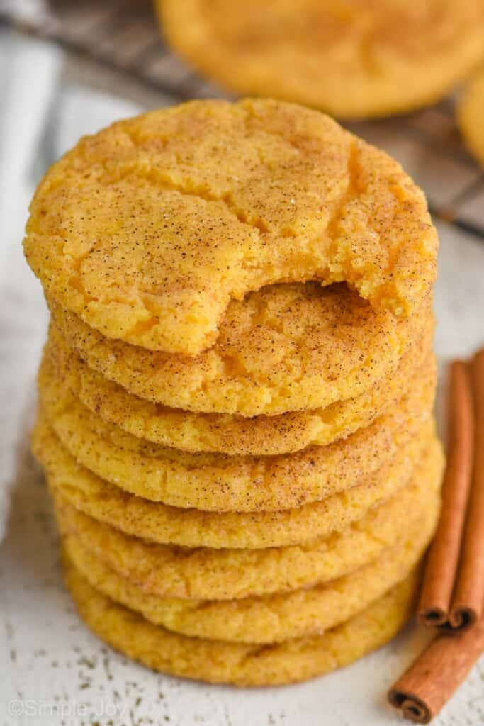 stack of pumpkin snickerdoodle cookies with the top one missing a bite, two cinnamon sticks sitting next to it