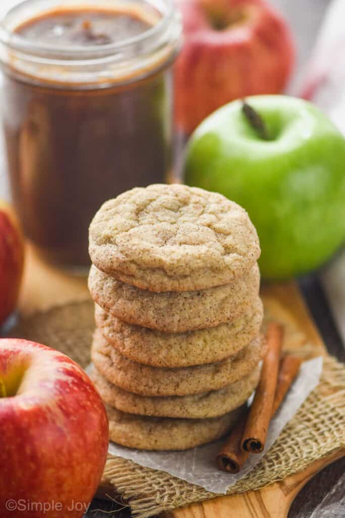 a stack of apple butter cookies with a jar of apple butter and an apple in the background
