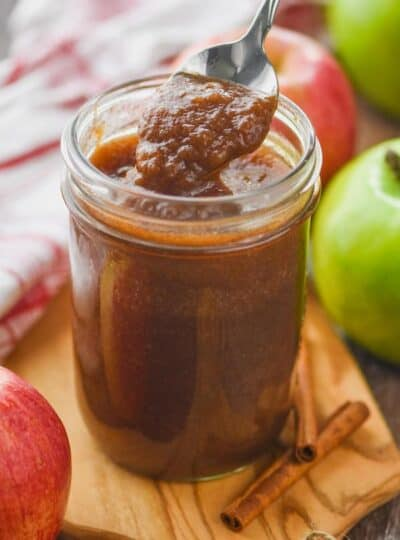 a small mason jar of an apple butter recipe that is being spooned up