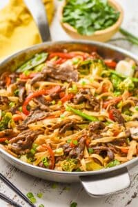skillet of beef lo mein garnished with scallions and sesame seeds