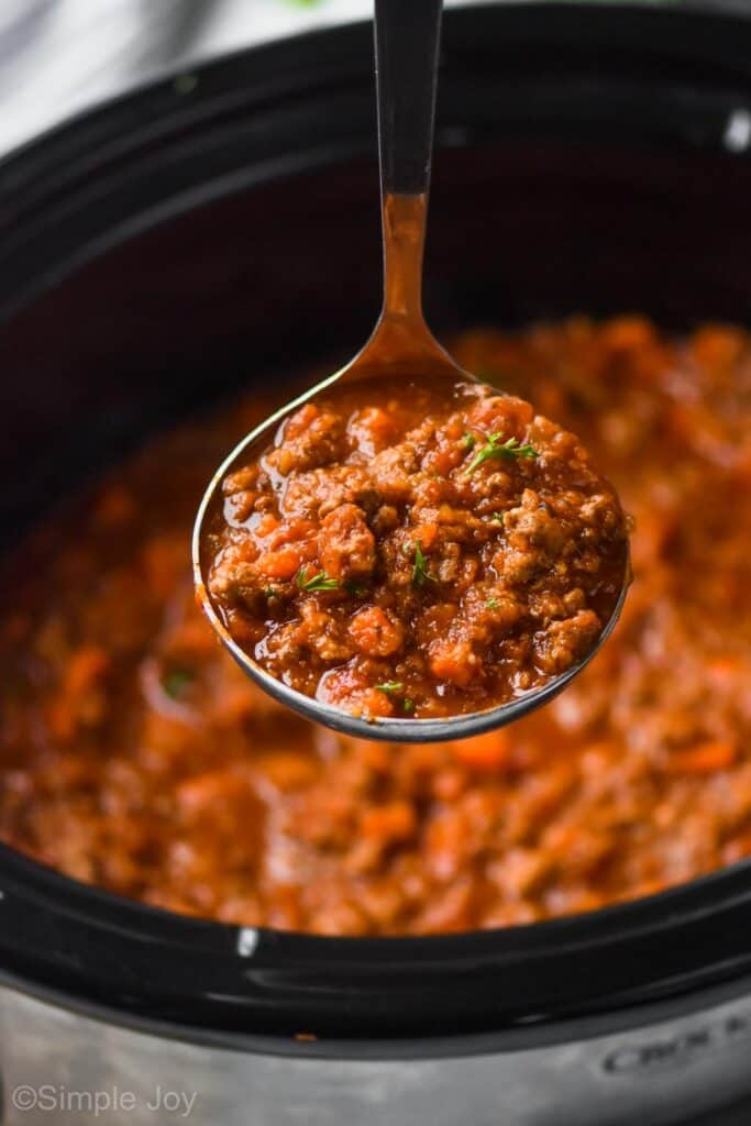 bolognese sauce recipe being ladled out of a slow cooker