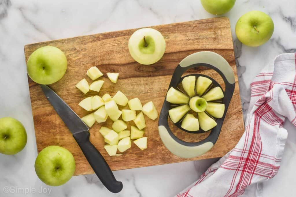 overhead view of a cutting board, cutting peeled apples with an apple corer