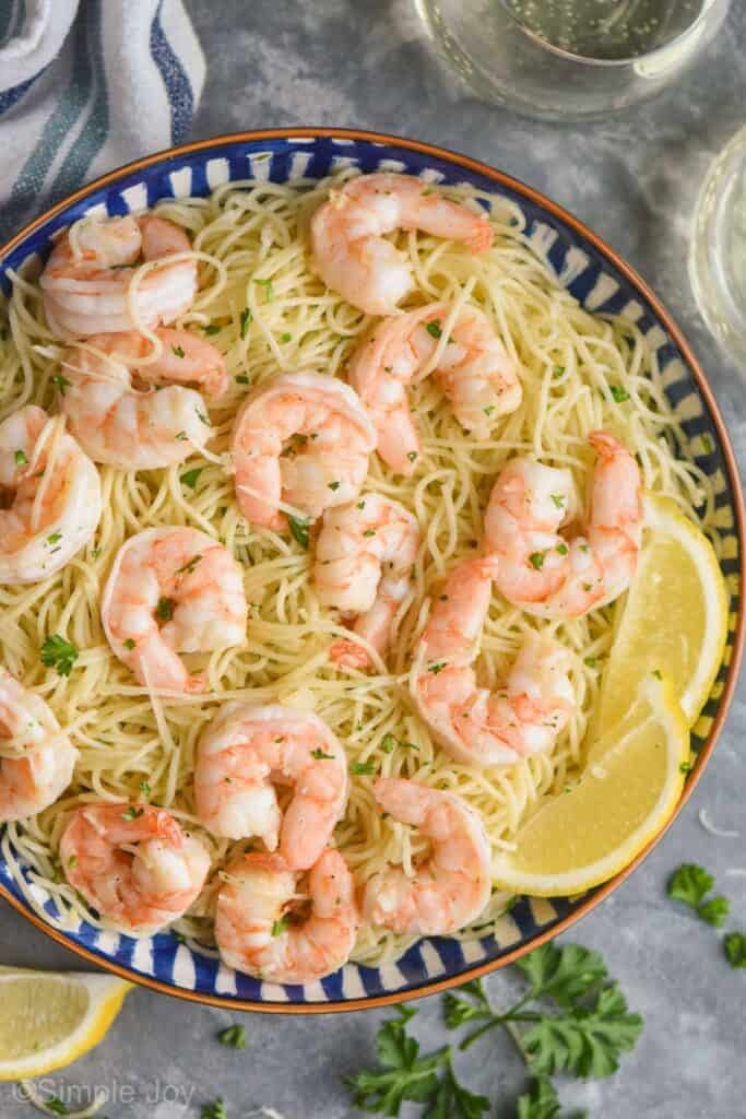 overhead view of a bowl of shrimp scampi garnished with lemon wedges, parsley, and parmesan cheese