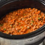 slow cooker bolognese in a crockpot garnished with fresh parsley