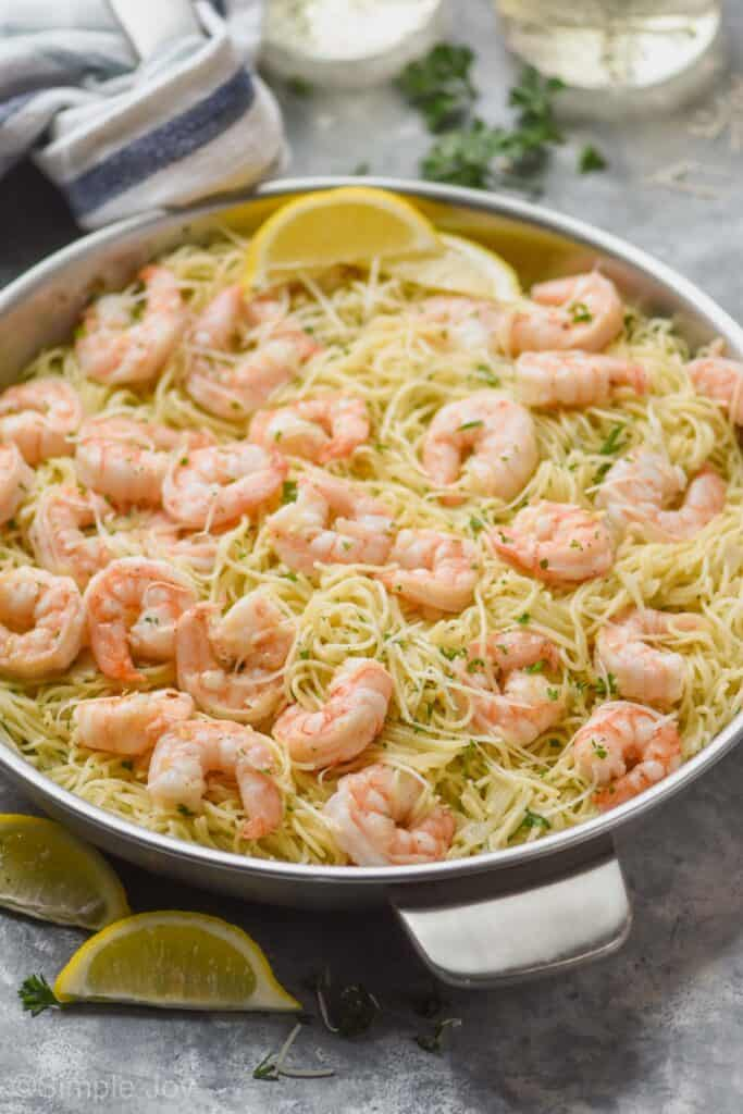 side view of a skillet full of shrimp scampi with angel hair pasta