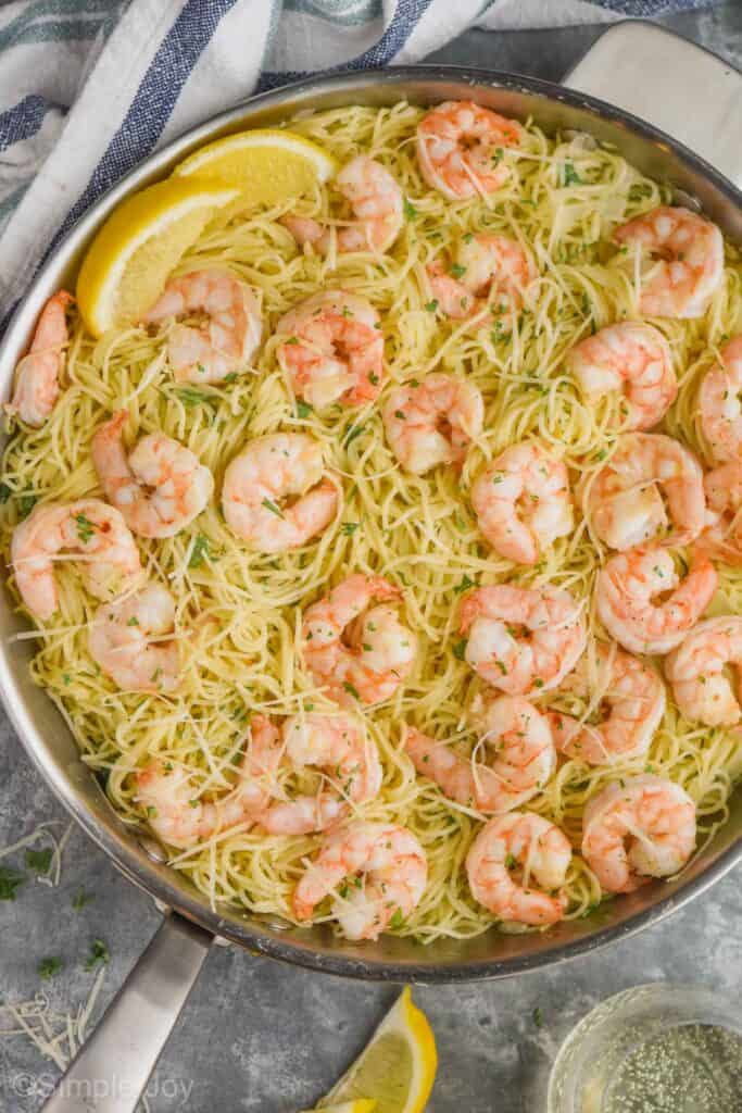 overhead view of a skillet full of shrimp scampi topped with fresh parsley and freshly grated Parmesan cheese and garnished with lemon wedges