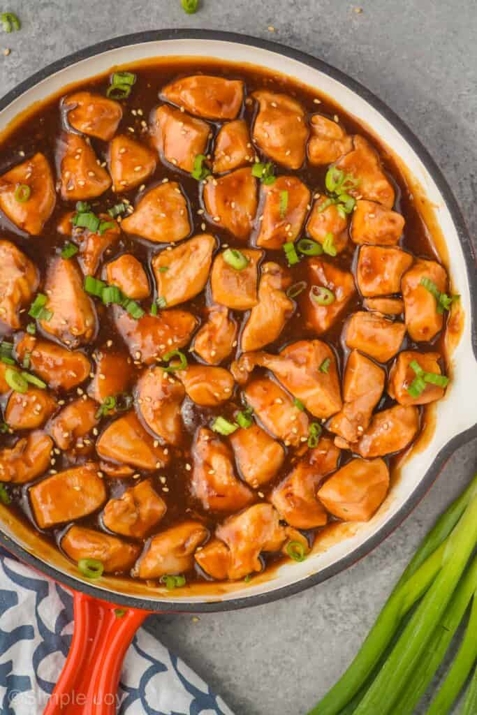 overhead view of sticky chicken in a skillet garnished with sesame seeds and green onion