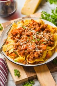 a plate of pappardelle bolognese sauce garnished with freshly grated parmesan and parsley