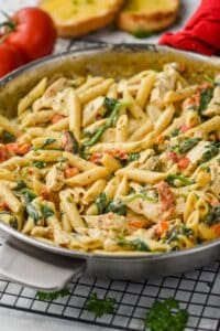 side view of a pan of creamy tuscan chicken pasta in a skillet with tomatoes and toasted garlic bread in the background