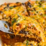 piece of cheese enchilada casserole being lifted out of baking dish
