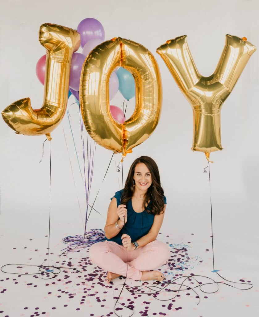 woman sitting cross legged on the floor holding balloons that spell out JOY