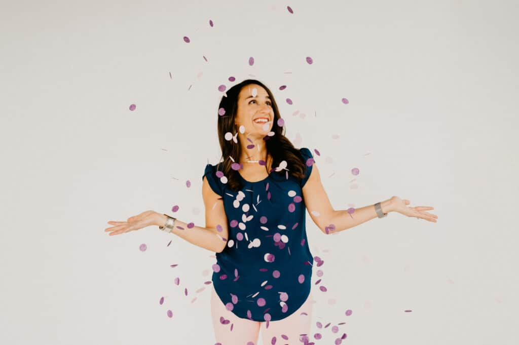woman standing under a shower of pink and purple confetti with her arms out