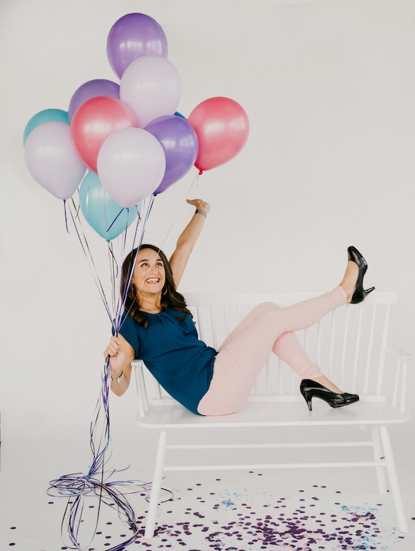 woman sitting on a bench with her feet in the air, holding a bouquet of balloons against a white background