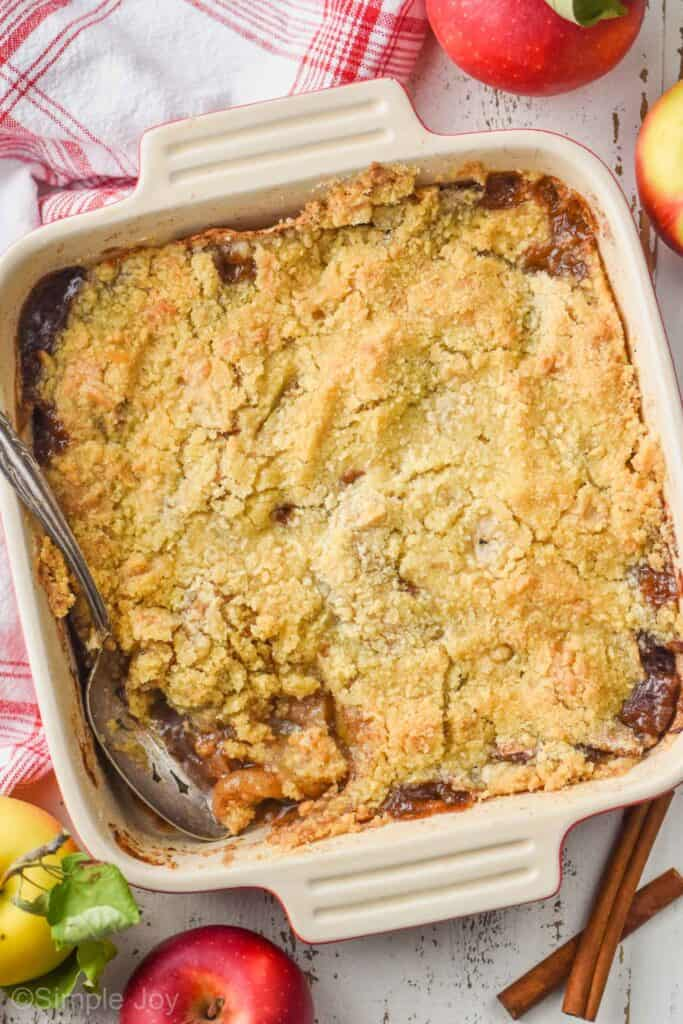 overhead view of square baking dish holding apple crisp recipe with a spoon digging in