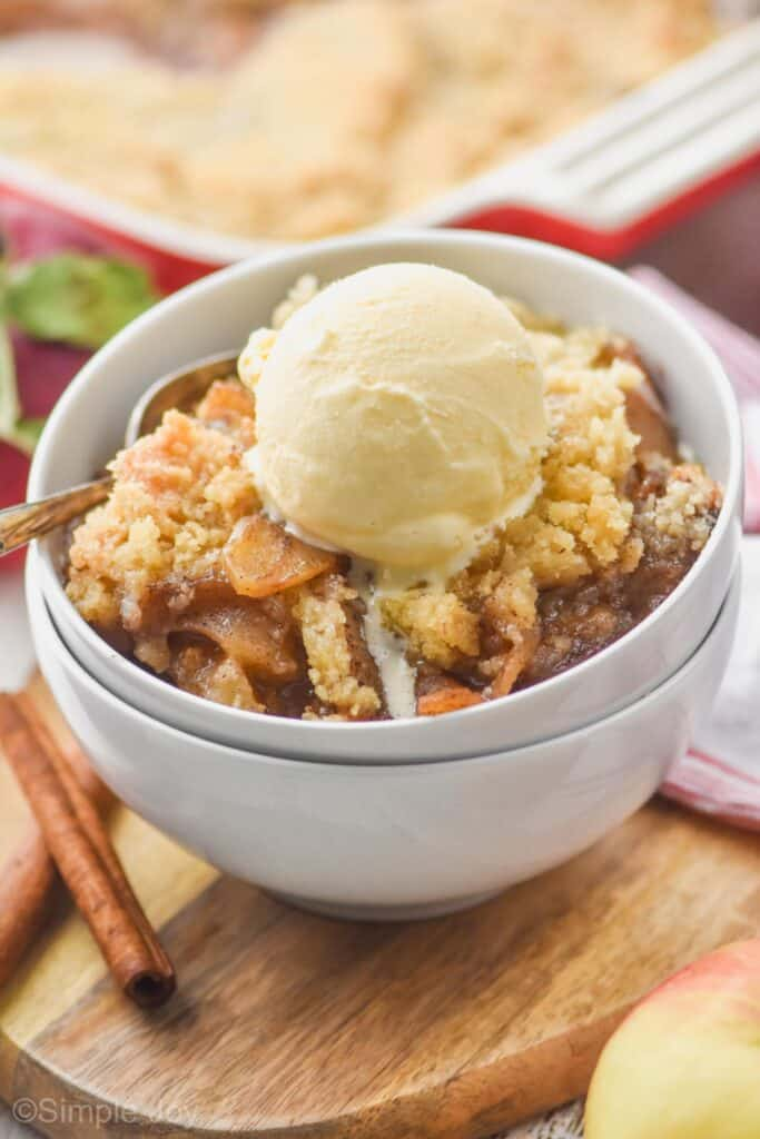two white bowls stacked holding best apple crisp recipe topped with ice cream, baking dish in the background