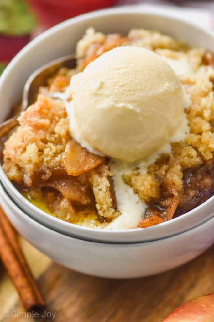 two white bowls stacked holding easy apple crisp recipe topped with ice cream