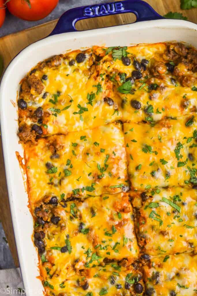 close up overhead of easy enchilada casserole in a baking dish that has been cut into pieces