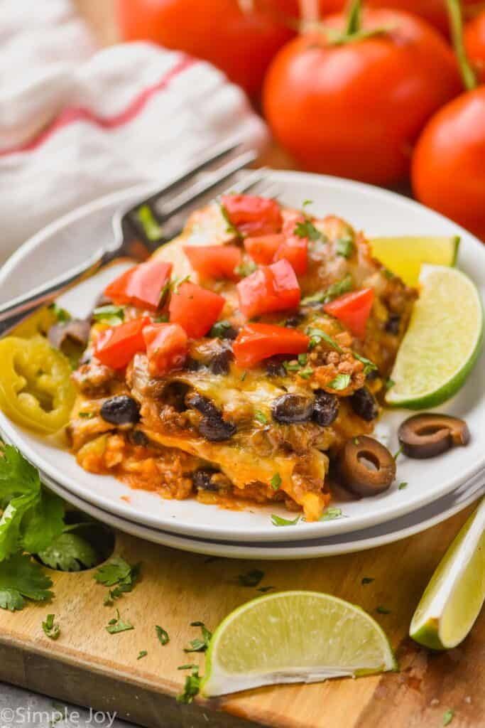 enchilada casserole recipe cut (like a lasagna) on a plate and topped with fresh tomatoes and olive slices