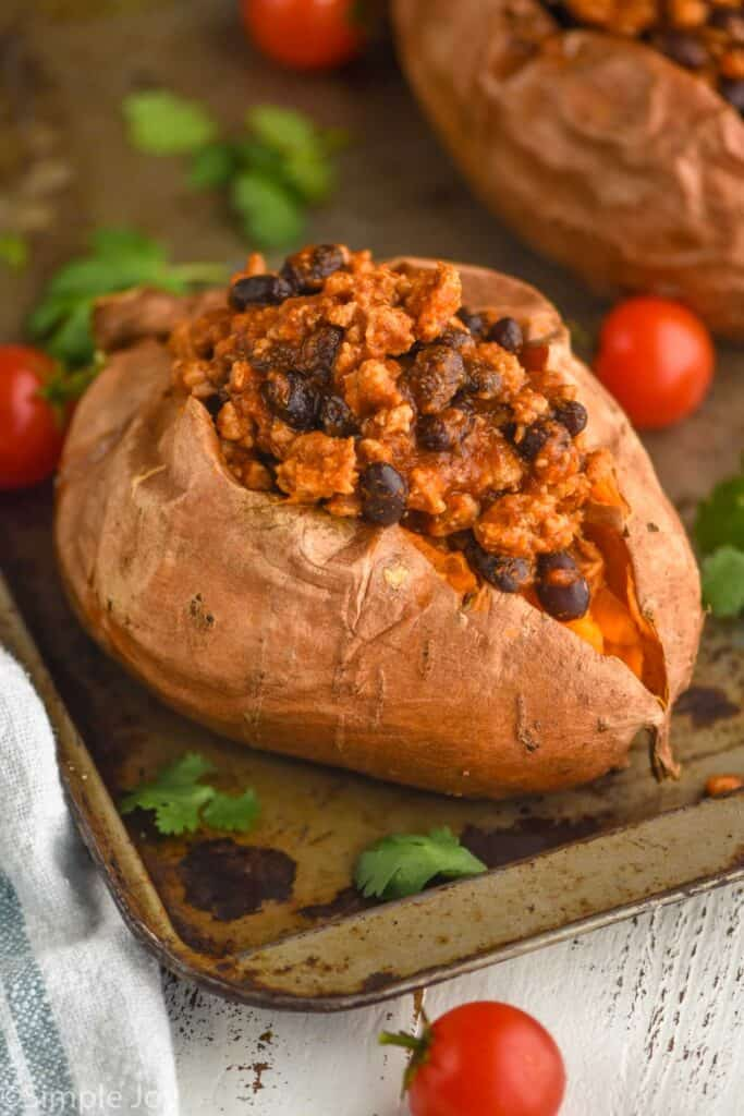 a whole sweet potato that has been split in half and topped with taco meat and black beans