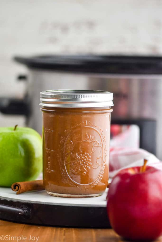 a mason jar full of applesauce in front of a slow cooker