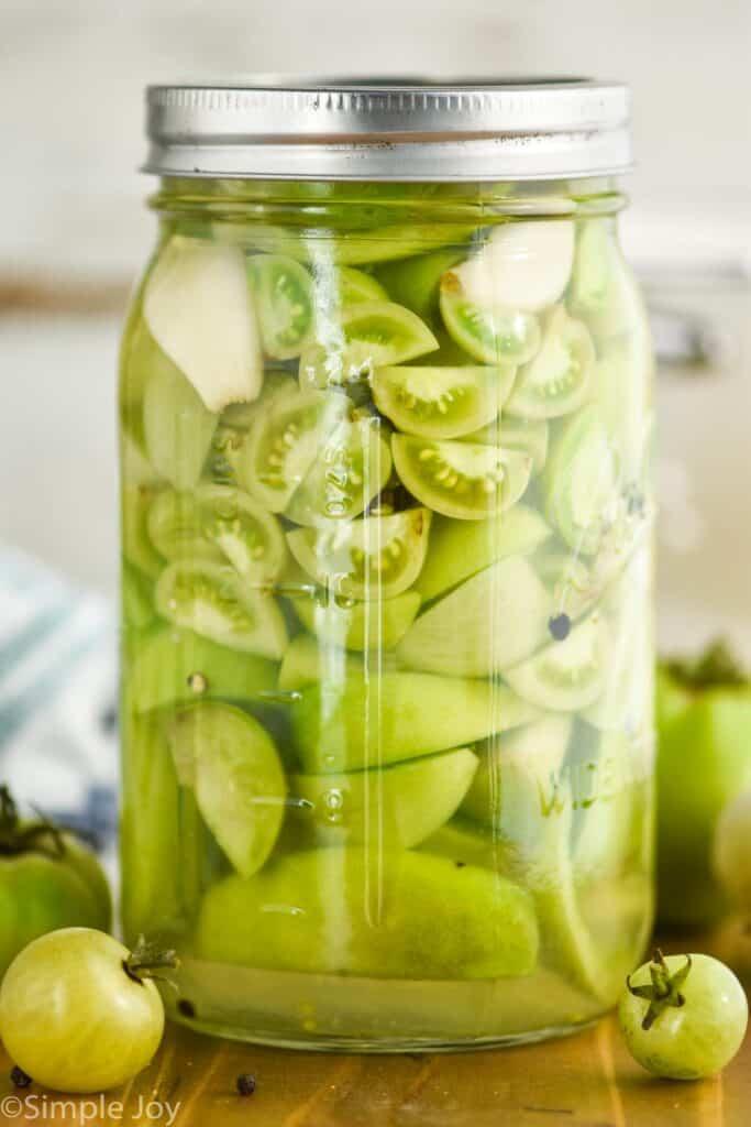 a mason jar full of pickled green tomatoes
