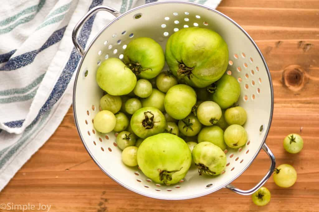 overhead view view of a colander full of green tomatoes