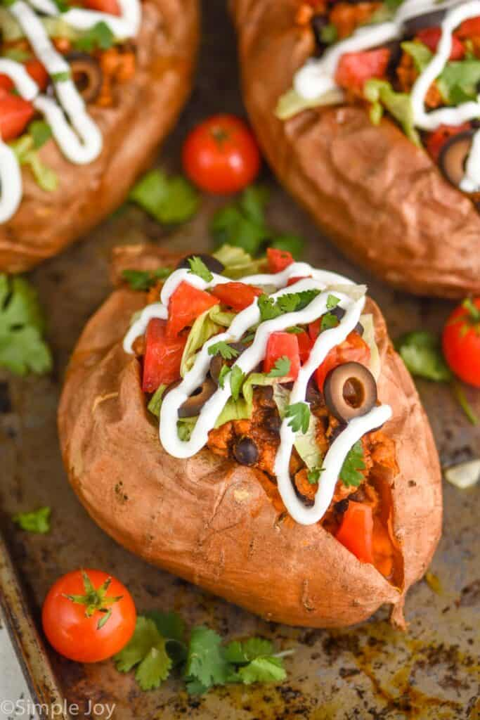 close look at a whole sweet potato that has been topped with taco meat, olives, sour cream, cilantro, and diced tomatoes