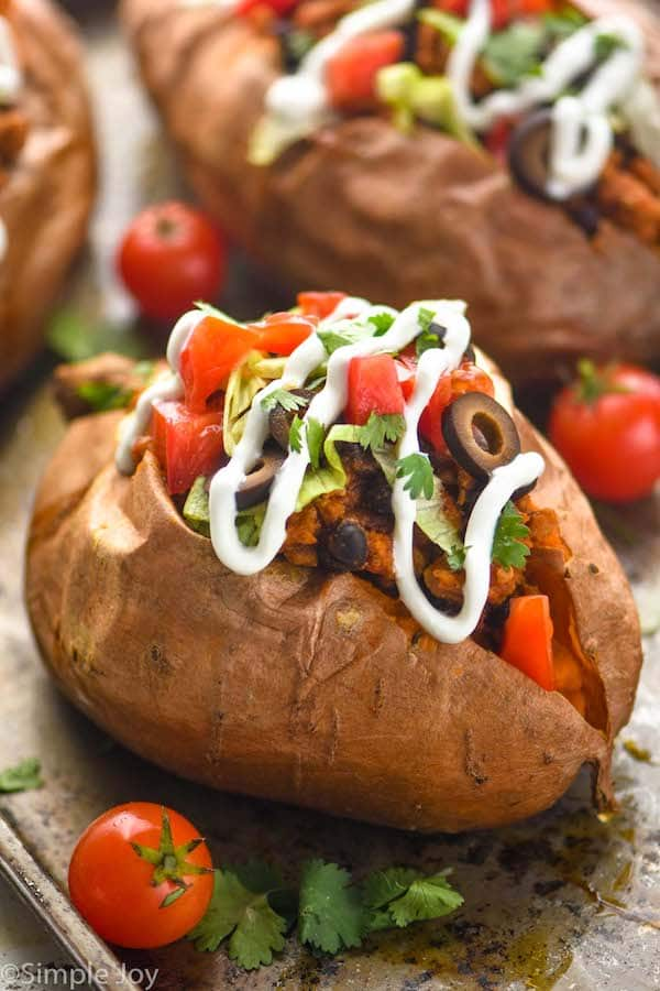 close up of a taco stuffed sweet potato on a baking sheet that has been topped with sour cream, cilantro, sliced olives, diced tomatoes, and lettuce