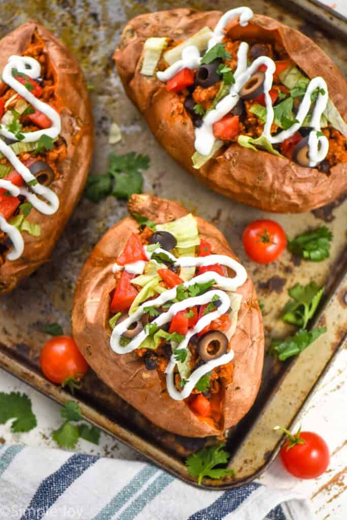 overhead view of taco stuffed sweet potato recipe on a baking sheet topped with sour cream, cilantro, tomatoes, and lettuce
