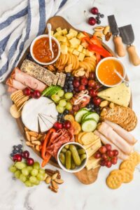 an overhead view of a charcuterie board with cheeses, meats, crackers, vegetables, fruits, and nuts