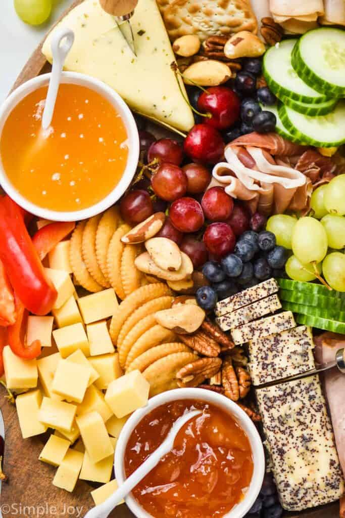 a close up of a charcuterie board with cheeses, dips, crackers, berries, and vegetables