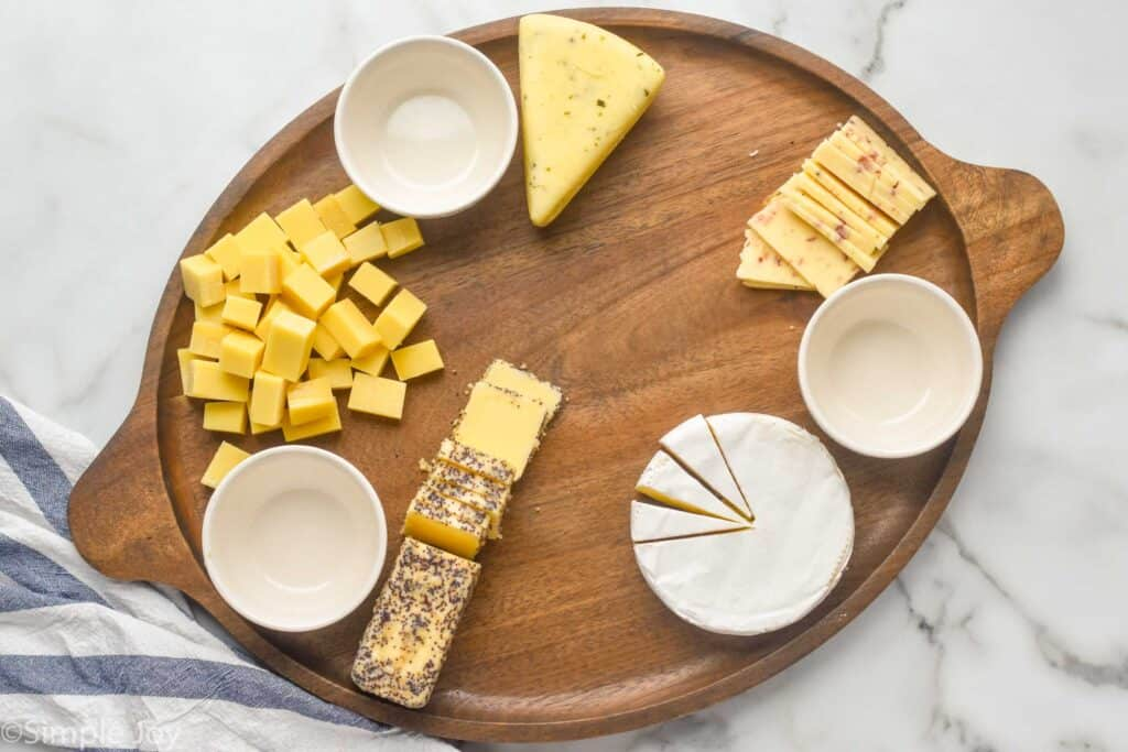 a large wooden tray with three white bowls for condiments and cut up cheeses