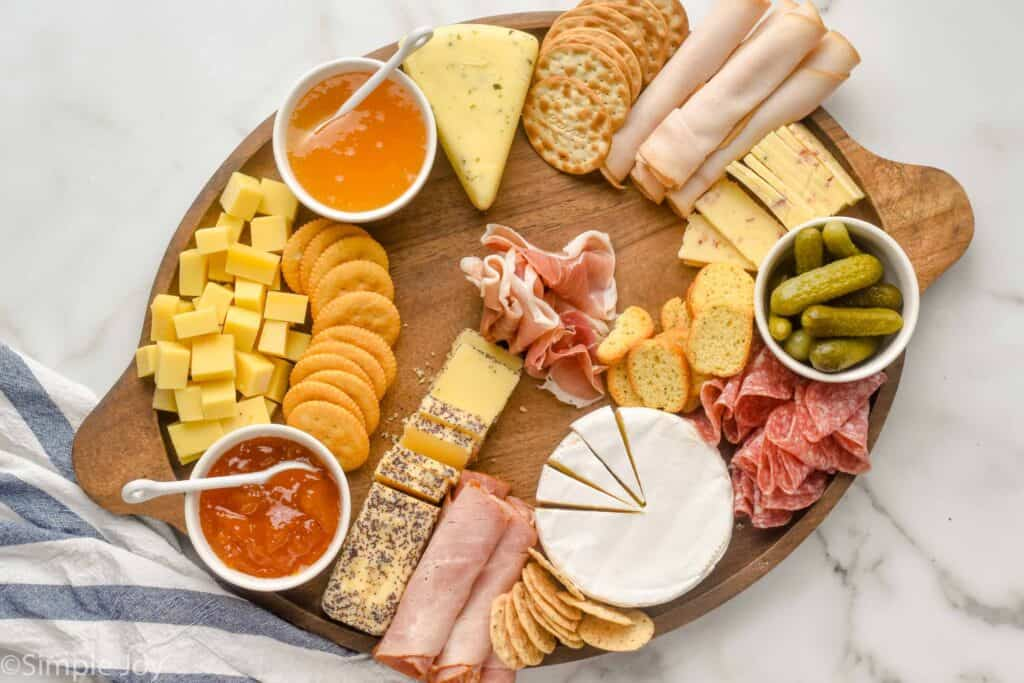 a large wooden tray with bowls of condiments, cut up cheese, deli meat, and crackers