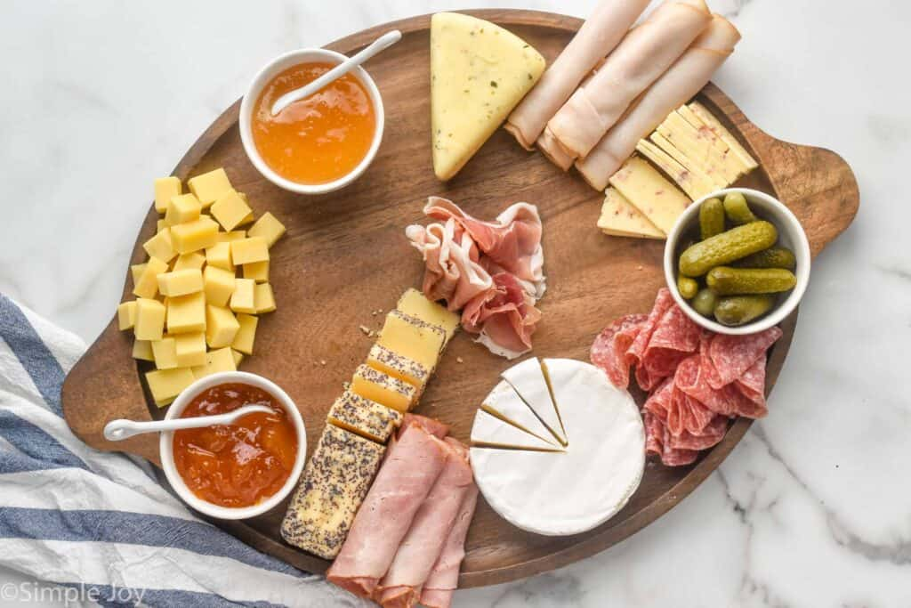 a large wooden tray with bowls for condiments, deli meats, and cheeses