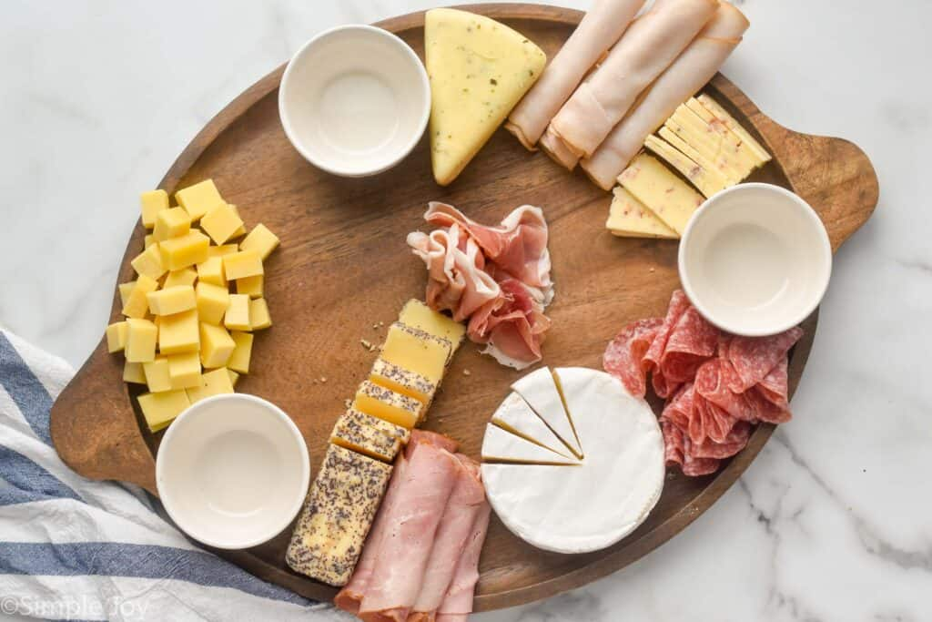 a large wooden tray with three white bowls, deli meats, and four blocks of cheese cut