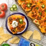 overhead look at sheet pan nachos next to a small plate of nachos, an open bag of Tostitos and a jar of Tostitos salsa
