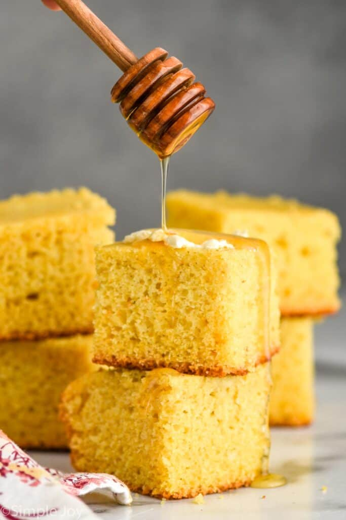honey wand dripping honey over two pieces of stacked cornbread