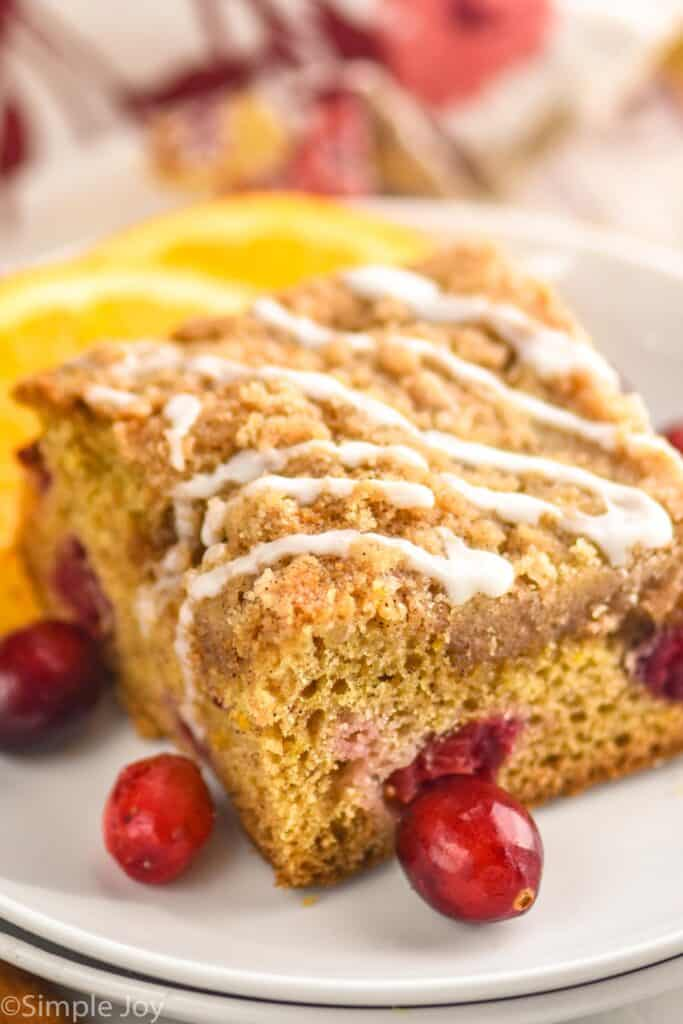a piece of cranberry orange coffee cake up close on a plate with icing drizzled on top