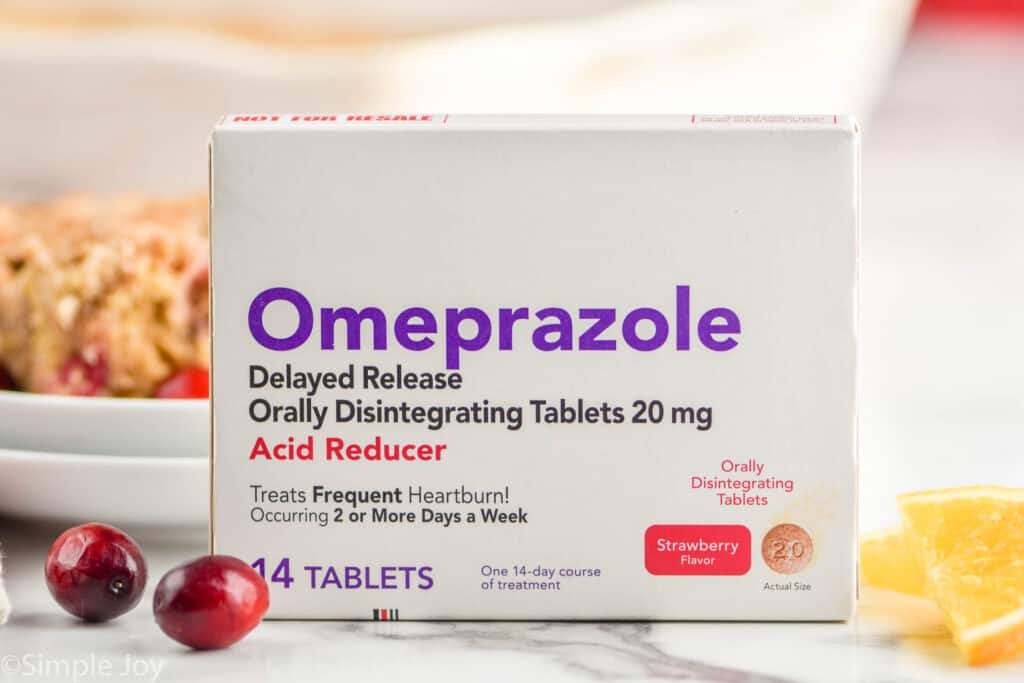 a box of ompeprazole odt next to two cranberries