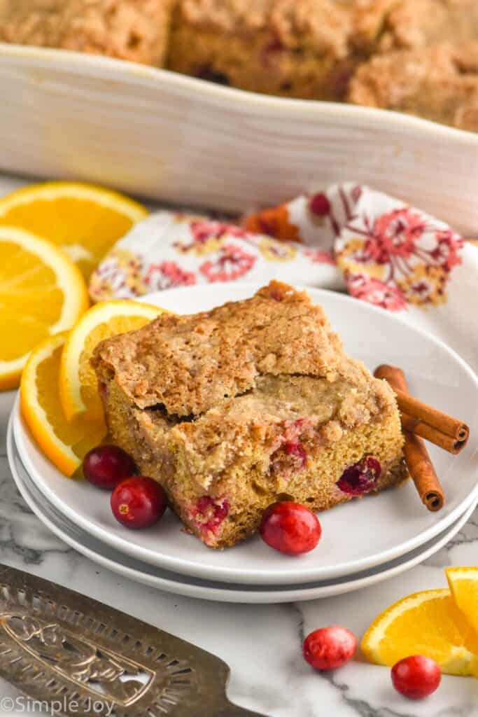 a piece of coffee cake recipe on a plate with cinnamon sticks, cranberries, and orange slices