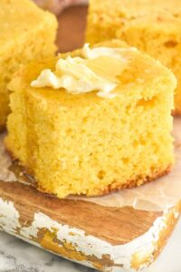 close up picture of cornbread recipe topped with butter and honey