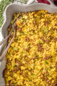 overhead view of a baking dish with cornbread stuffing recipe with two utensils sticking put