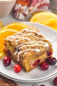 piece of cranberry orange coffee cake that has had icing drizzled across the top of it